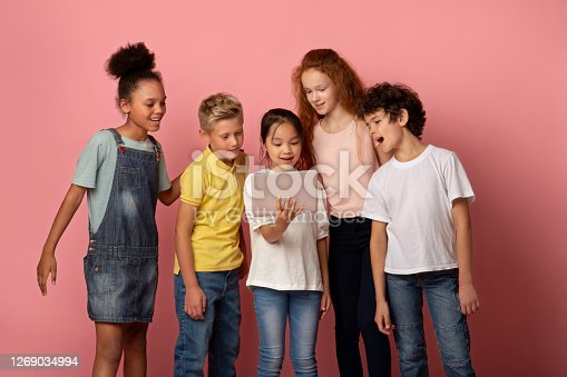 Online schooling concept. Happy children watching interesting web lesson on tablet computer over pink background