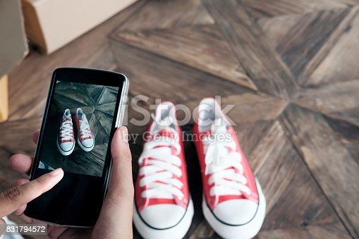 istock Online seller use mobile phone take a photo of product for upload to website online shop. 831794572