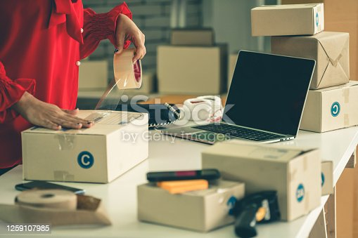868776578 istock photo Online seller works at home office and packs shipping delivery box to customer. 1259107985