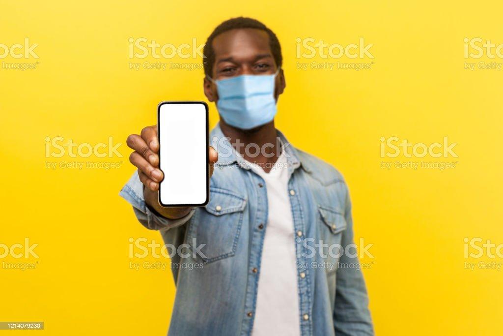 Online-Service, Technologie. Porträt von zufriedenen glücklichen jungen Mann mit medizinischer Maske stehen halten Handy und lächelnd breit in der Kamera. - Lizenzfrei Abschirmen Stock-Foto