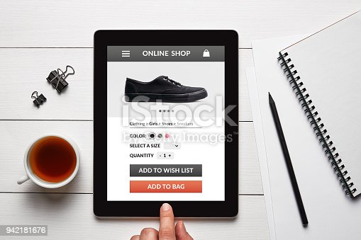 1134879628 istock photo Online shop concept on tablet screen on white wooden table 942181676