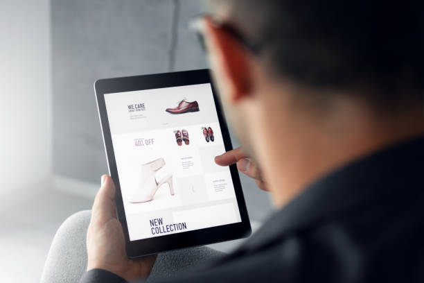 Online shop - Digital tablet Male hand is browsing an online shop on digital tablet which is selling shoes. e commerce stock pictures, royalty-free photos & images