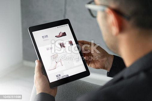 Male hand is browsing an online shop which is selling shoes on digital tablet.