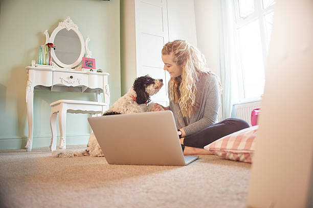 online shopper with her best friend a young woman is sitting crosslegged on the floor of her bedroom using her laptop to buy something . her family dog comes to say hello. dog at dressing table