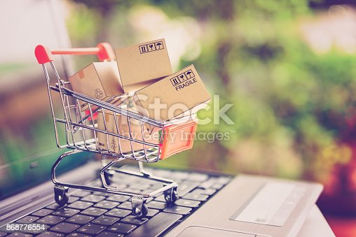 istock Online shopping and delivery service concept. Paper cartons in a shopping cart on a laptop keyboard, this image implies online shopping that customer order things from retailer sites via the internet. 868776554