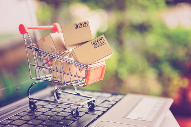 Online shopping and delivery service concept. Paper cartons in a shopping cart on a laptop keyboard, this image implies online shopping that customer order things from retailer sites via the internet. stock photo