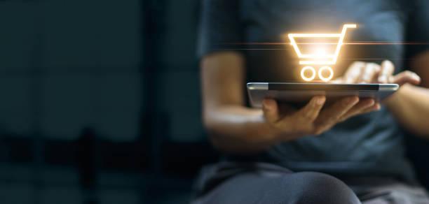 online-shopping und digitales marketing-konzept, frau mit digitalen tablet mit warenkorb-symbol auf dem bildschirm auf dunklem hintergrund. - konsum stock-fotos und bilder