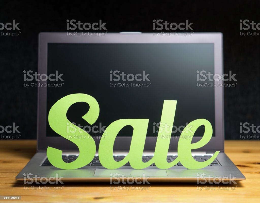 Online shopping and e-commerce concept. Laptop computer with sale letters cut from cardboard paper. Discount and bargain prices on internet store or shop. Marketing material for promotion campaign. zbiór zdjęć royalty-free