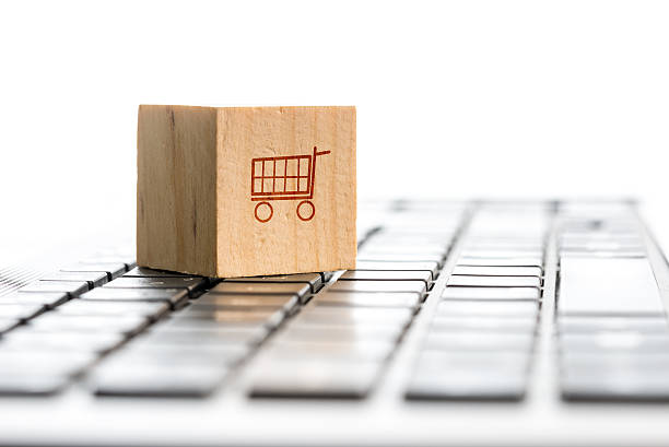 Online shopping and e-commerce concept Online shopping and e-commerce concept with a wooden block with an icon of a shopping cart standing on a computer keyboard, viewed low angle with copyspace. home shopping stock pictures, royalty-free photos & images