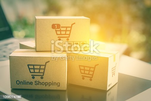 868776578 istock photo Online shopping and ecommerce over internet concept : Boxes with shopping cart logo on smart tablet and laptop computer, depicts consumers always buy goods or things directly from online retail store. 1058274786
