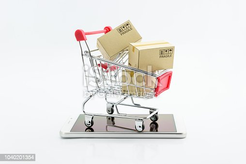 868776578istockphoto Online shopping and ecommerce via internet concept : Boxes in a shopping cart or metal trolley on a white mobile smartphone . Consumer always buy or shop goods and things from online retail stores . 1040201354