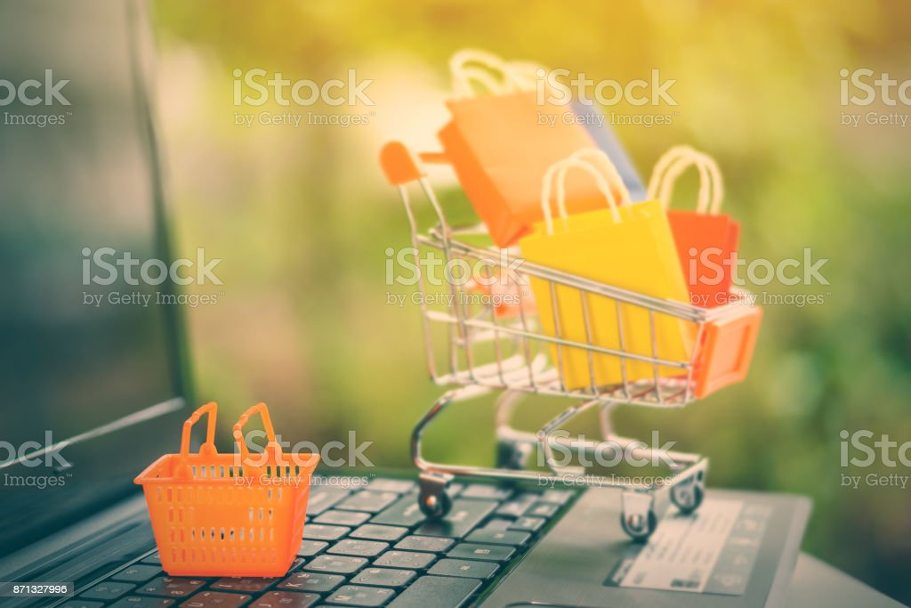 Online shopping and ecommerce via internet concept : Mini orange basket on a laptop computer keyboard with paper shopping bags in a shopping cart behind. Consumer always buy things from online stores. - Foto stock royalty-free di Acquisti a domicilio