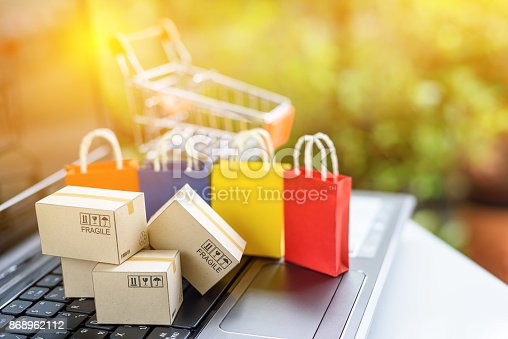 istock Online shopping and ecommerce via internet concept : Paper boxes and color shopping bags on a laptop computer keyboard with empty shopping cart behind. Consumer always buy things from online stores. 868962112