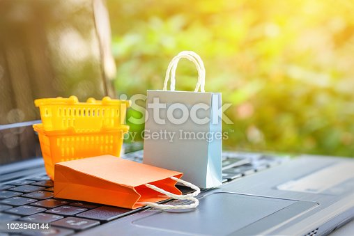 868776578istockphoto Online shopping and ecommerce via internet concept : Paper shopping bags and orange plastic shopping basket on laptop computer. Consumer always buys or shops goods and things from online retail stores 1024540144
