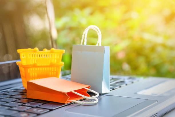 online-shopping und e-commerce via internet-konzept: papier-tragetaschen und orange kunststoff warenkorb auf laptop-computer. verbraucher immer kauft oder geschäfte waren und dinge aus online-einzelhandel - kostenlose webseite stock-fotos und bilder