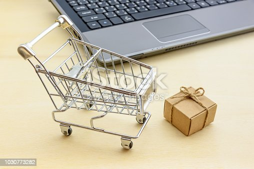 868776578istockphoto Online shopping and ecommerce via internet concept : Shopping cart and a present / paper gift box near laptop. Consumer always buys / shops and sends goods or things directly from online retail stores 1030773282