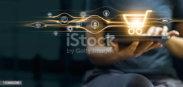 Online shopping and payment, Man using tablet with shopping cart icon, Digital marketing, Banking and finance on dark blue background.