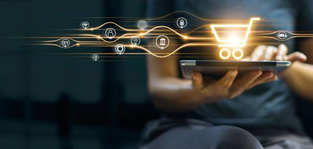 online-shopping und bezahlen, mann mit tablet mit warenkorb-symbol, digital marketing, banking und finanzen auf dunkelblauem hintergrund. - konsum stock-fotos und bilder