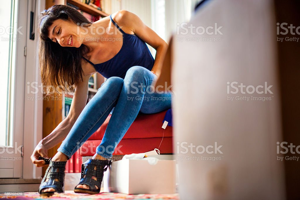 Online shopping at home - Woman unboxing clothes stock photo