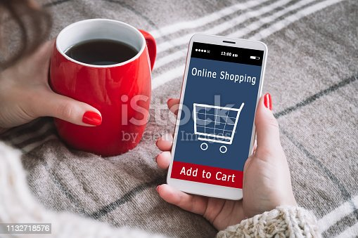 A woman is shopping at the online store. Shopping cart icon. Ecommerce. Eshop.