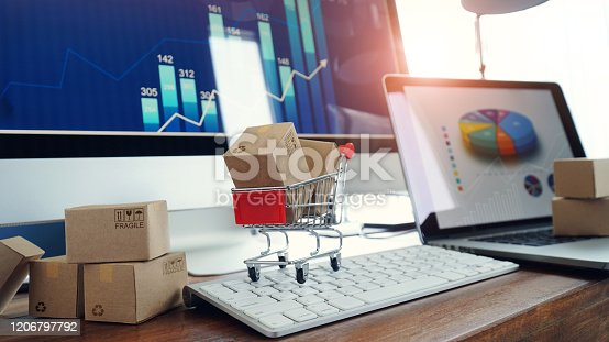 Online shopping, Boxes on table and in trolley on a laptop keyboard and business graph growth on screen background, Electronic commerce.