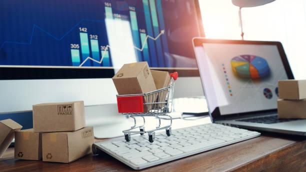 achats en ligne, boîtes sur la table et en chariot sur un clavier d'ordinateur portable et la croissance de graphique d'affaires sur le fond d'écran, commerce électronique. - graph photos et images de collection