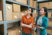 vintage retro film color photo of online shopping company female colleague working together and using mobile computer pad checking warehouse stock.