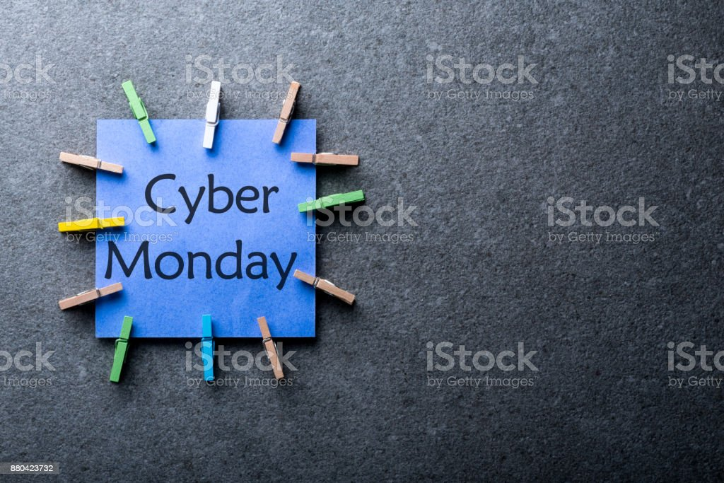 Online shopping concept. A blue paper label with the text Cyber Monday written in it against a dark gray background. Day with biggest Sale. Mockup stock photo