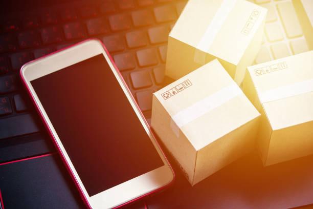 online-shopping konzept e-commerce delivery service zu kaufen. quadratischen kartons einkaufen auf laptop-tastatur, zeigt die bestellung des kunden über das internet und smartphone. - iphone gratis stock-fotos und bilder
