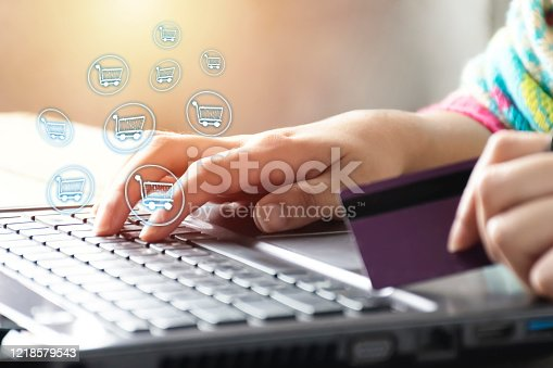 Online shopping concept. Women are buying online with a credit card. Soft focus of young woman of freelancer working using laptop computer, Communication icons, notifications Shopping cart
