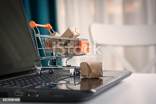 istock Online shopping concept. Shopping cart, small boxes, laptop on the desk 692898468