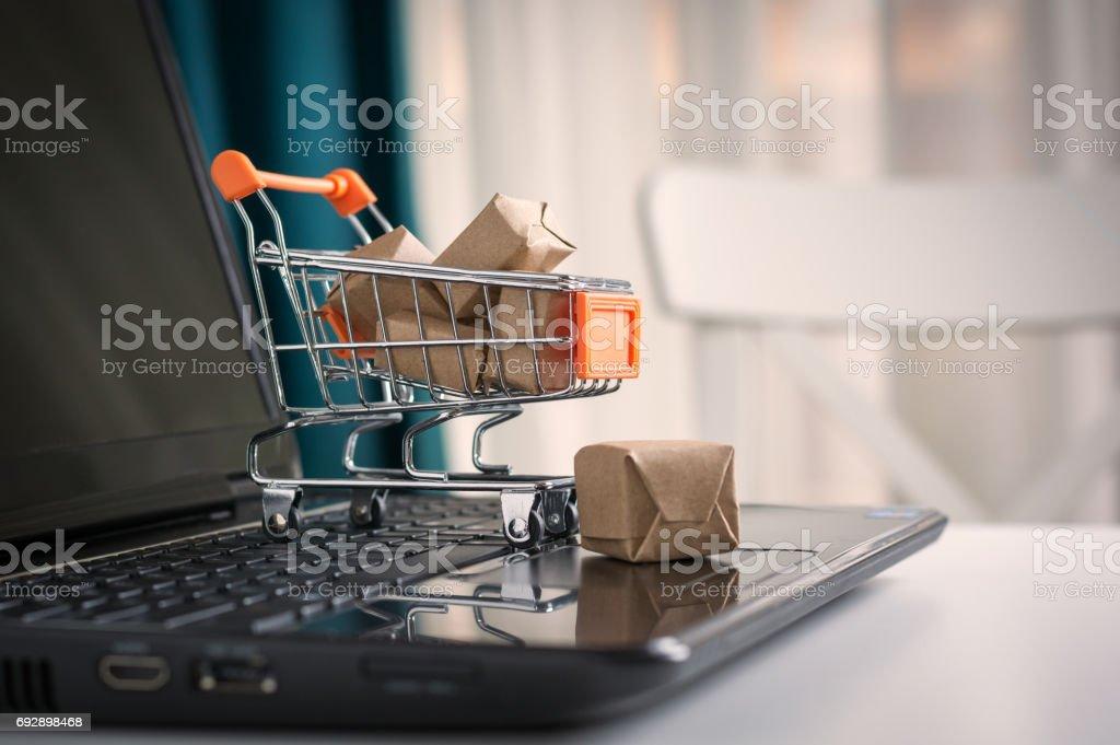 オンライン ショッピングの概念。ショッピング カート、小箱、机の上のノート パソコン ストックフォト