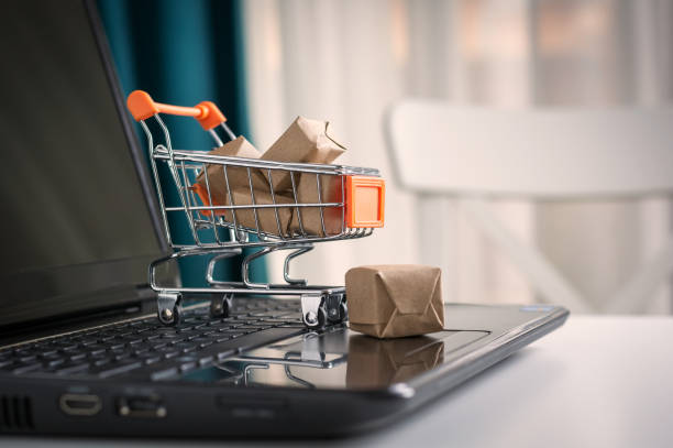 online shopping concept. shopping cart, small boxes, laptop on the desk - e commerce stock photos and pictures