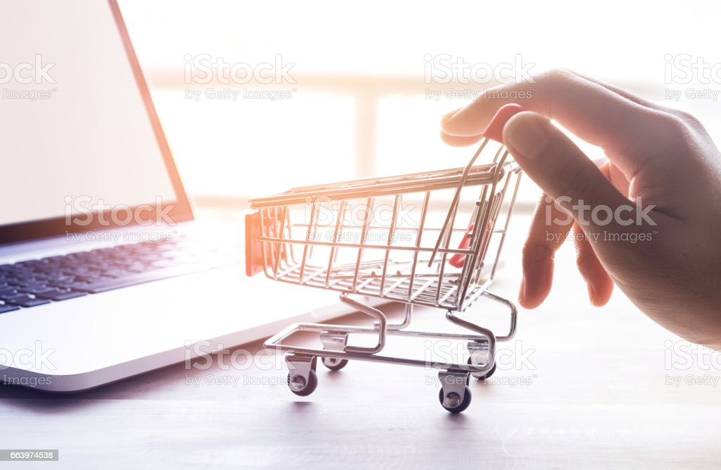 Online shopping concept with hand and cart stock photo