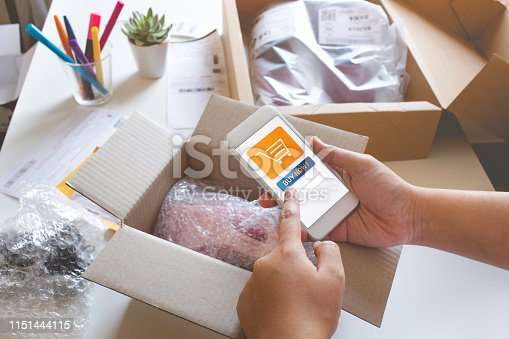 868776578 istock photo Online shopping concepts with young female buying product with website on smartphone and some her product on table. 1151444115