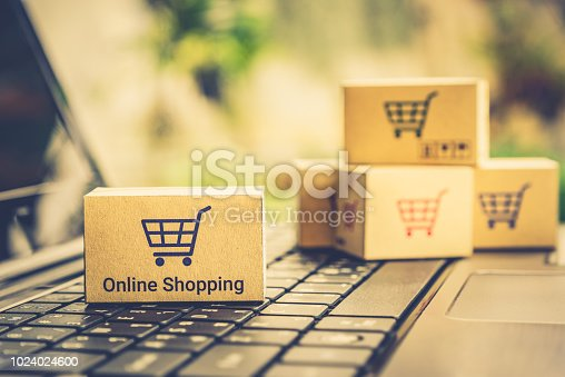 868776578istockphoto Online shopping / ecommerce and delivery service concept : Paper cartons with a shopping cart or trolley logo on a laptop keyboard, depicts customers order things from retailer sites via the internet. 1024024600