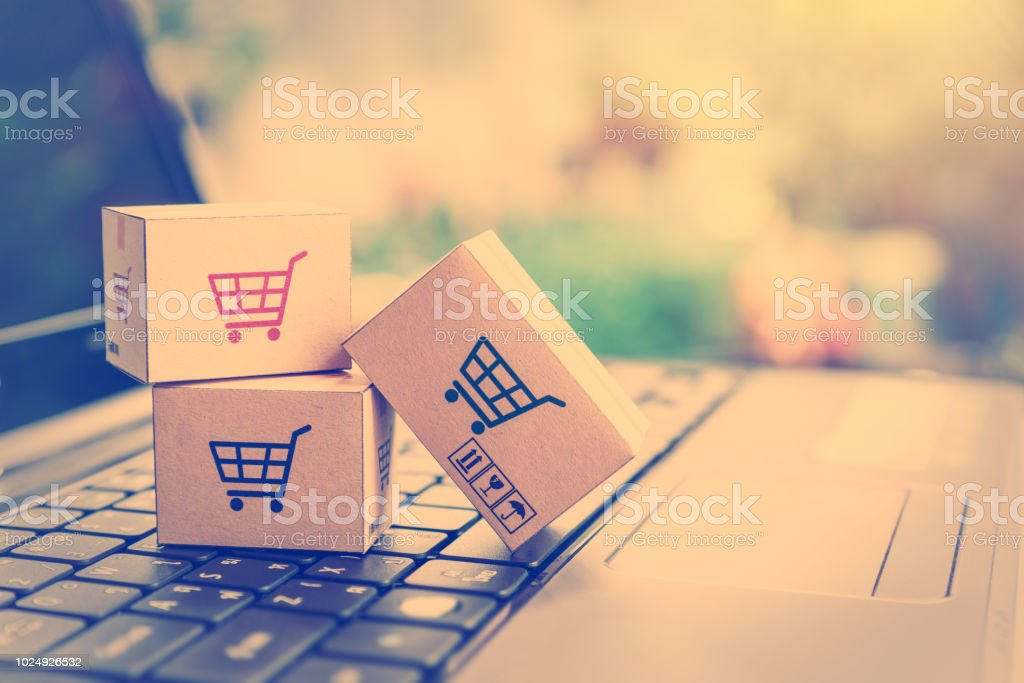 Online shopping / ecommerce and delivery service concept : Paper cartons with a shopping cart or trolley logo on a laptop keyboard, depicts customers order things from retailer sites via the internet. - Royalty-free Accessibility Stock Photo