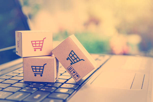 Online shopping / ecommerce and delivery service concept : Paper cartons with a shopping cart or trolley logo on a laptop keyboard, depicts customers order things from retailer sites via the internet. stock photo