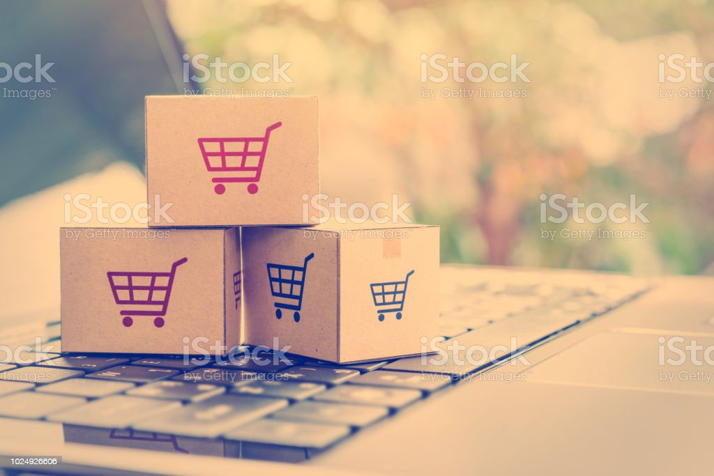 013187fb Online shopping / ecommerce and delivery service concept : Paper cartons  with a shopping cart or trolley logo on a laptop keyboard, depicts  customers order ...