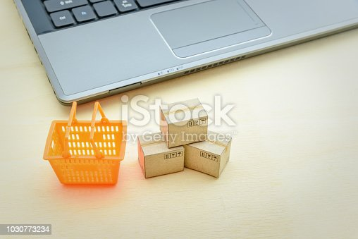 868776578istockphoto Online shopping / ecommerce and delivery service concept : Paper cartons or boxes, plastic shopping basket near a laptop computer, depicts customers order things from retailer sites over the internet. 1030773234