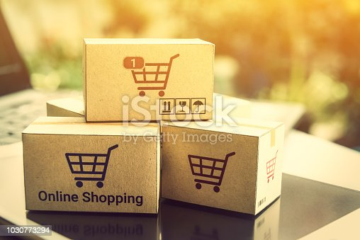 868776578istockphoto Online shopping / ecommerce and delivery service concept : Paper cartons with a shopping cart or trolley logo on a laptop keyboard, depicts customers order things from retailer sites via the internet. 1030773294