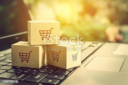 868776578istockphoto Online shopping / ecommerce and delivery service concept : Paper cartons with a shopping cart or trolley logo on a laptop keyboard, depicts customers order things from retailer sites via the internet. 1030773316