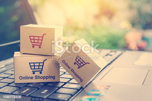 868776578istockphoto Online shopping / ecommerce and delivery service concept : Paper cartons with a shopping cart or trolley logo on a laptop keyboard, depicts customers order things from retailer sites via the internet. 1030773326