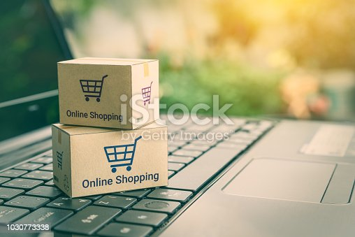 868776578istockphoto Online shopping / ecommerce and delivery service concept : Paper cartons with a shopping cart or trolley logo on a laptop keyboard, depicts customers order things from retailer sites via the internet. 1030773338