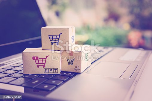 868776578istockphoto Online shopping / ecommerce and delivery service concept : Paper cartons with a shopping cart or trolley logo on a laptop keyboard, depicts customers order things from retailer sites via the internet. 1030773342