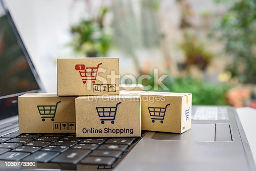 868776578istockphoto Online shopping / ecommerce and delivery service concept : Paper cartons with a shopping cart or trolley logo on a laptop keyboard, depicts customers order things from retailer sites via the internet. 1030773360