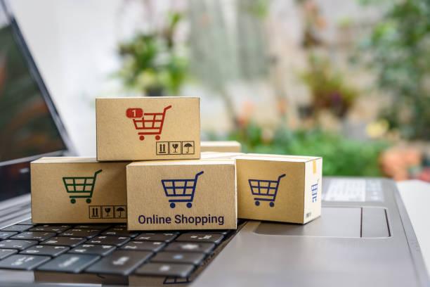 online-shopping / e-commerce und lieferung service konzept: papier kartons mit einem einkaufswagen oder trolley-logo auf einer laptoptastatur, zeigt kunden bestellung dinge von händler-websites im internet. - kostenlose webseite stock-fotos und bilder