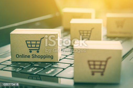 868776578istockphoto Online shopping / ecommerce and delivery service concept : Paper cartons with a shopping cart or trolley logo on a laptop keyboard, depicts customers order things from retailer sites via the internet. 1030773418