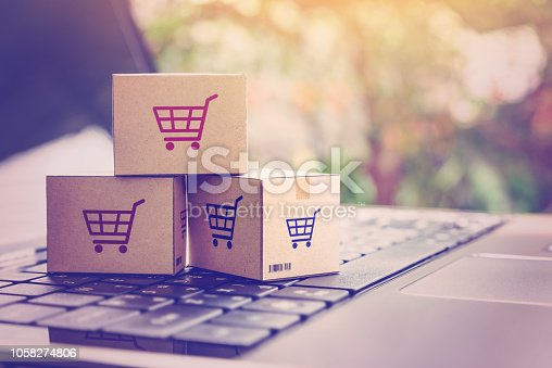 868776578 istock photo Online shopping / ecommerce and delivery service concept : Paper cartons with a shopping cart or trolley logo on a laptop keyboard, depicts customers order things from retailer sites via the internet. 1058274806