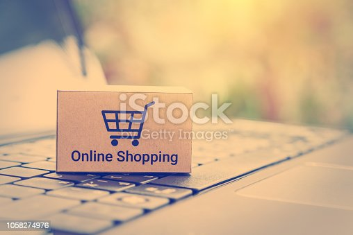 868776578 istock photo Online shopping / ecommerce and delivery service concept : Paper cartons with a shopping cart or trolley logo on a laptop keyboard, depicts customers order things from retailer sites via the internet. 1058274976